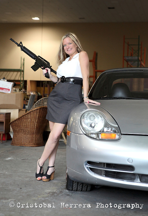 Annette Boves Grasso, from J. Sugarman Auction Corp, poses holding a fake rifle, next to the Porsche convertible used in the Burn Notice show, are seen at the Coconut Grove Convention Center before the Burn Notice auction, on Monday August 26, 2013. The most-iconic and most-recognizable cars, props and apparel used during seven seasons of the show will be sold during the auction. Staff Photo Cristobal Herrera