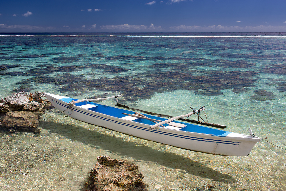 A canoe docked to a rock on the transparent water of Moorea Island.<br /> <br /> This photo was published on MSN worldwide https://www.msn.com/en-in/news/photos/tropical-paradise-the-beauty-of-french-polynesia/ss-BBEkuRm#image=12