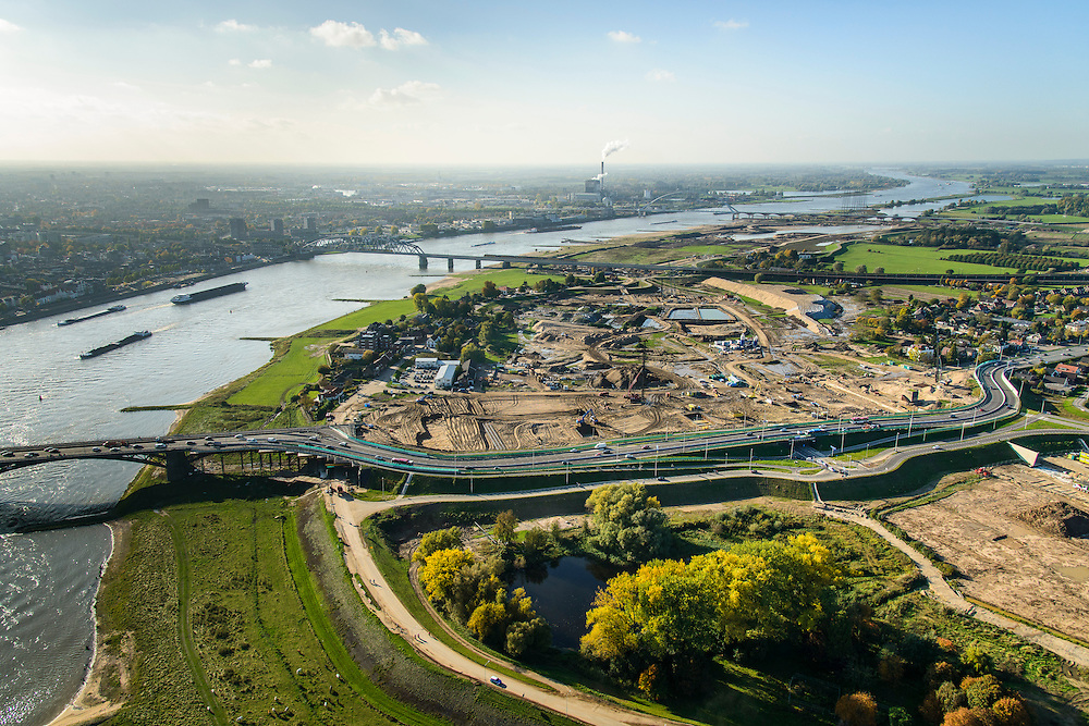 Nederland, Gelderland, Nijmegen, 24-10-2013; rivier de Waal met (de toerit naar ) de Waalbrug, gezien vanuit het Oosten, daarachter de spoorbrug met fietspad (De Snelbinder) en tenslotte de nieuwe stadsbrug van Nijmegen De Oversteek. Rechts van de rivier grondwerkzaamheden voor de dijkteruglegging Lent (Ruimte voor de Rivier). De dijken worden landinwaarts verplaats en er wordt een nevengeul gegraven. De huizen op de dijk blijven bestaan en komen te liggen op het Stadseiland Veur-Lent Nijmegen. In de verte de rookpluimen van de energiecentrale Electrabel Nederland.<br /> First bridge the Waal bridge on the river Waal, next the railway bridge with cycle path De Snelbinder (The Luggage strap) and finally the new city bridge of Nijmegen De Oversteek (The Crossing). Right of the river groundwork for the Dike relocation of Lent (project Ruimte voor de Rivier: Room for the River). <br /> luchtfoto (toeslag op standaard tarieven);<br /> aerial photo (additional fee required);<br /> copyright foto/photo Siebe Swart.