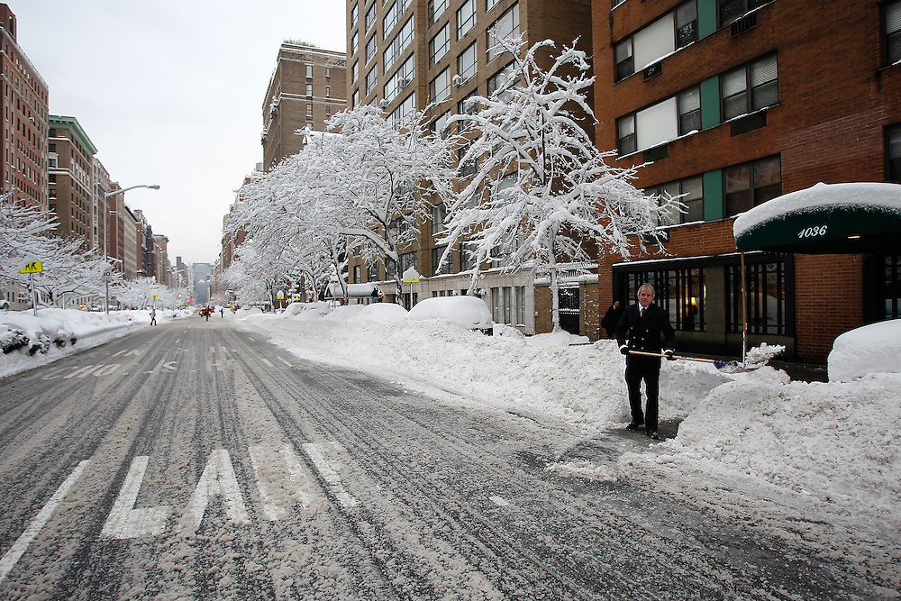A New York City Park Ave building doorman Patrick shoveling snow in New York City..Photo by Joe Kohen