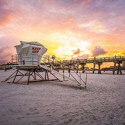 Pensacola Beach lifeguard tower five and Gulf Pier sunrise photo on Casino Beach. Pensacola Beach Florida is a coastal city on Santa Rosa Island in the Emerald Coast of the Southeastern United States of America. Copyright ⓒ 2018 Paul Velgos with All Rights Reserved.