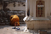 A Buddhist monk bows in prayer at the base of a stupa at Wat Gate Khar Rnam temple in Chiang Mai, Thailand.