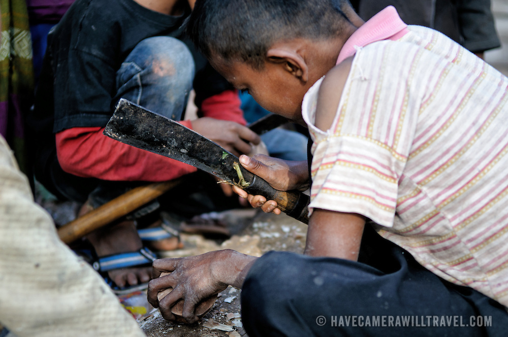 A boy in a village in northern Laos carves a wooden top with a knife to create a spinning top used with a string and turned into a sport. The metal tip of an umbrella spine is inserted into the tip of the spinning top to provide a solid point.