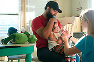 Johny Hendricks and his wife, Christina, give medicine to their sick two-year-old daughter, Adli, at their home in Midlothian, Texas on February 27, 2014.
