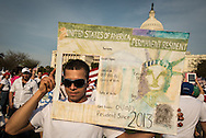 Robert Morales from Annapolis, MD, originally from El Salvador, places his head in a fake legal document as he and other Immigration activists gather on the West Lawn of the U.S. Capitol during a Rally for Citizenship in Washington D.C. April 10, 2013. Activists are wanting Congress to act on proposals that would allow a path to citizenship for the 11 million immigrants without legal status. Photo Ken Cedeno