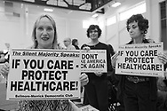 "Westbury, New York, USA. January 15, 2017. L-R, AUDREY CIUFFO, HELENE MANAS, and FRANCINE GOLDSTEIN, members of Bellmore-Merrick Democratic Club, are holding protest signs at the ""Our First Stand"" Rally against Republicans repealing the Affordable Care Act, ACA. ""The Silent Majority Speaks"" posters say: ""IF YOU CARE - PROTECT HEALTHCARE!"" and: ""DON'T MAKE AMERICA SICK AGAIN."""