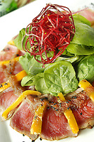 Seared Tuna carpaccio with yellow peppers , tamarind sauce and salad greens