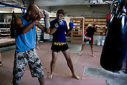 "Shuki (left) coaches Ilya (center) as Eran (right) trains with punching bags in Rompo Muay Thai Gym, Khlong Toei, Bangkok city, Thailand on 14th December 2009..Shuki Rosenzweig, aged 40, is a professional Muay Thai Boxing fighter (champion) and trainer who has lived for 9 years in Thailand. He is famous in Israel as the authority of this sport. Started at the age of 12 in boxing in Israel, Jerusalem. Used to work in the fish market. His father is a 'legend' in Jerusalem fish market. Shuki stopped working with his dad about 13 years ago. He has opened some muay thai gyms in Thailand in the past. He currently has about 5 Israeli fighters under his training in Bangkok, besides fighters of other nationalities. Shuki found religion in Bangkok with Chabad about 4 years ago. He never misses Shabbat and loves to sing the songs of prayer, priding himself with a good voice. ""Chabad integrates all Jews. it keeps us together. When at Chabad, we are at home, united with people of the same culture, language and beliefs""..Eran Schwartz, aged 30, from Jerusalem, has been training for 8 years. He trains for endurance, fitness and fun, although he has fought in one competition in Bangkok the last time he was here. ""Eran is very talented, technically adept, wise and has a 'good eye' for fights"" says Shuki. This time Eran is staying 3 and a half months in Thailand to train, travel, and write scripts for a TV show and a cartoon series. He had studied economics and used to work in a bank in Israel before he came here. Eran's grandparents are religious but he grew up being secular. ""Chabad never pushes you to be religious. It is a relaxed place, they accept you for what you are"" says Eran. ""It is important to go for Shabbat for all Jews on travel."".Ilya Bashes, aged 27, from Herzeliya, Israel, has been fighting seriously for 5 years. He met Shuki in a muay thai seminar in Israel and decided immediately that he would come to Thailand to train under Shuki. ""I knew he was serious from the lo"