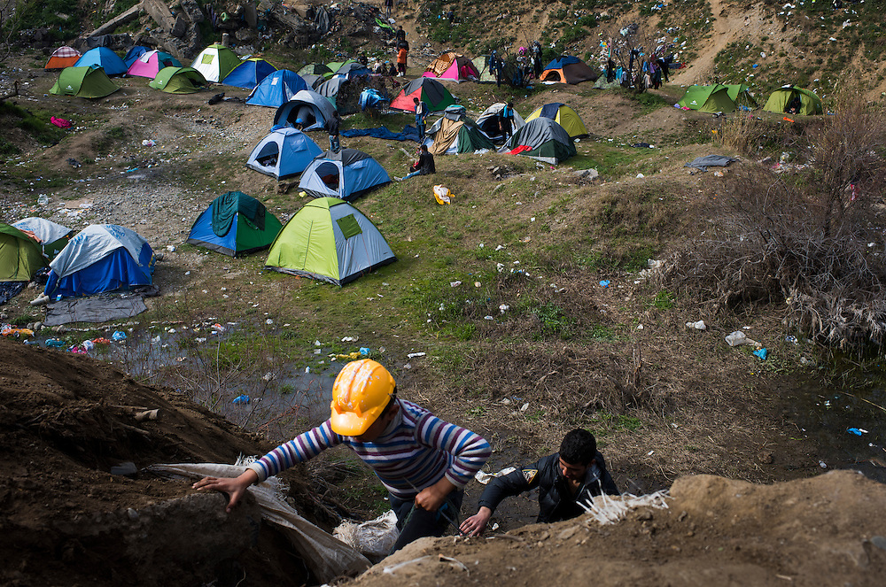 Migrants climb out of a pit where they are camped on the Macedonian (FYROM) border on March 6, 2016 in Idomeni, Greece.