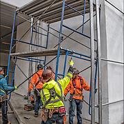 Workers assembling scaffolding to the top and around the outside of Lenox Health Greenwich Village building.<br /> <br /> The scaffolding company provides the scaffold and shoring erection and dismantle services.<br /> <br /> Scaffolding  is a temporary structure for holding workers and materials during the erection, repair, or decoration of a building.