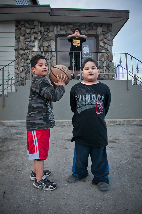 Fourteen year old, Tai Lolofietele, forms a basket with his arms for brothers Jericoh and Jerome, outside the Alaska Nazarene Church at 13th and E Street, Anchorage