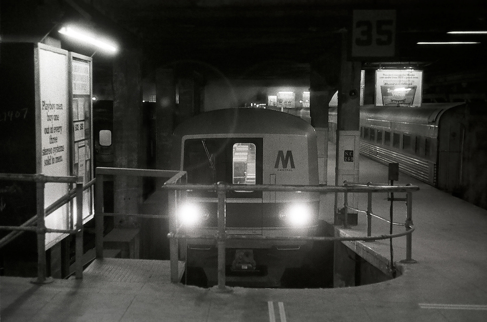Trains at the terminal of Grand Central. Geometrical composition. Striking details and contrasts. No passengers or people present. 1975. Black and white.
