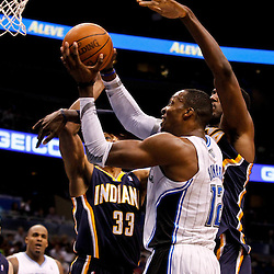 March 11, 2012; Orlando, FL, USA; Orlando Magic center Dwight Howard (12) is defended by Indiana Pacers small forward Danny Granger (33) and Indiana Pacers center Roy Hibbert (55) during the first quarter of a game at  Amway Center.   Mandatory Credit: Derick E. Hingle-US PRESSWIRE