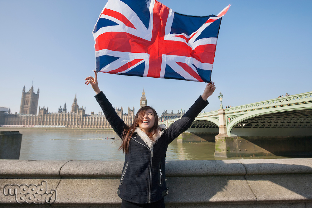 Happy woman holding British flag while standing against Big Ben at London; England; UK