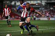 Jake Bidwell holding off Ainsley Maitland-Niles during the Sky Bet Championship match between Brentford and Ipswich Town at Griffin Park, London, England on 8 August 2015. Photo by Matthew Redman.