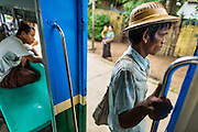 15 JUNE 2013 - YANGON, MYANMAR:  A man gets ready to get off the Yangon Circular Train as it pulls into his stop. The Yangon Circular Railway is the local commuter rail network that serves the Yangon metropolitan area. Operated by Myanmar Railways, the 45.9-kilometre (28.5 mi) 39-station loop system connects satellite towns and suburban areas to the city. The railway has about 200 coaches, runs 20 times and sells 100,000 to 150,000 tickets daily. The loop, which takes about three hours to complete, is a popular for tourists to see a cross section of life in Yangon. The trains from 3:45 am to 10:15 pm daily. The cost of a ticket for a distance of 15 miles is ten kyats (~nine US cents), and that for over 15 miles is twenty kyats (~18 US cents). Foreigners pay 1 USD (Kyat not accepted), regardless of the length of the journey.     PHOTO BY JACK KURTZ