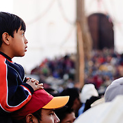 A young boy sits on his father's shoulders to watch the performance as part of Convite de 12 Dicembre in Chichicastengo. Chichicastenango is an indigenous Maya town in the Guatemalan highlands about 90 miles northwest of Guatemala City and at an elevation of nearly 6,500 feet. It is most famous for its markets on Sundays and Thursdays.