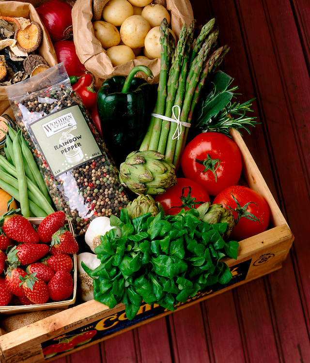 An assortment of fresh produce arranged in a wooden crate sits on a barn board background