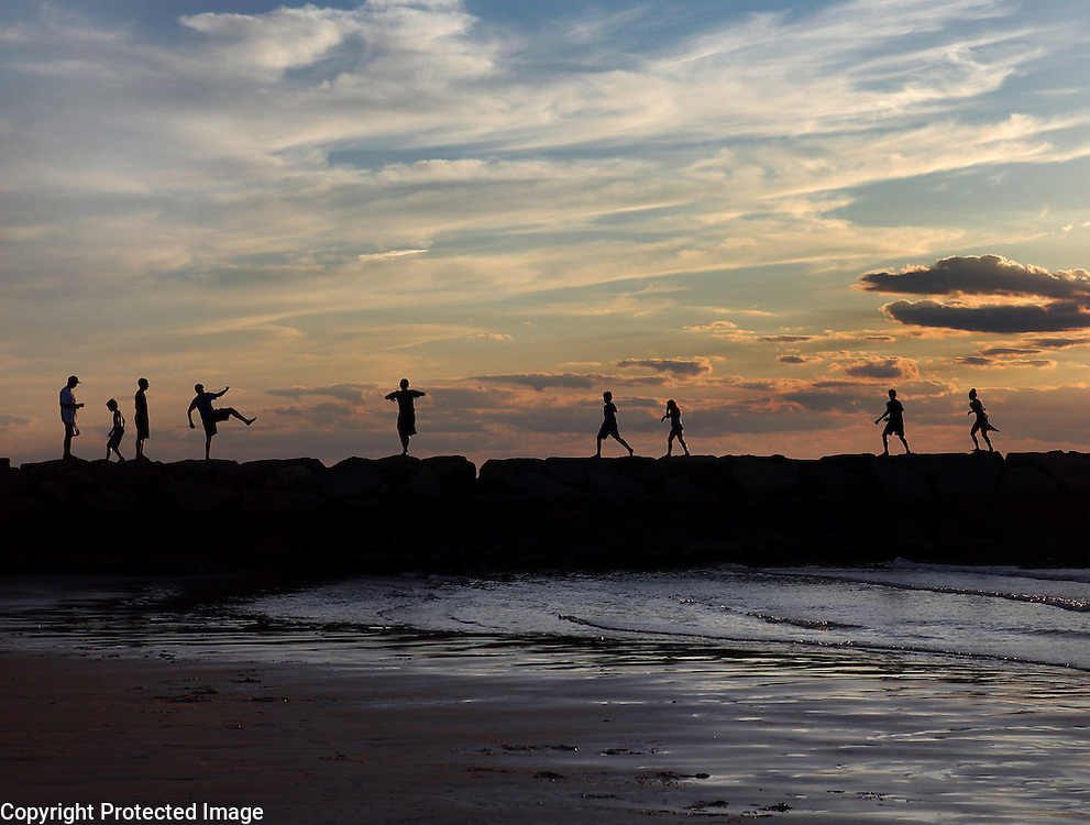 People are silhouetted on the jetty at Cold Storage Beach in East Dennis, MA.