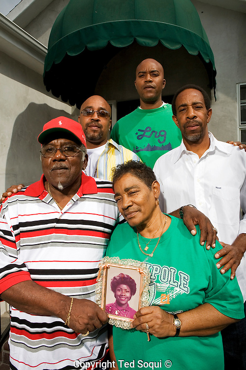 The Alexander family. Photo was shot at the home of Mary and Porter Alexander. Mary and Porter in front row, L to R in back are  Donnell, Darin, and Keevin. Mary is holding a photo of her daughter Alicia who was killed in 1988 at age 17.