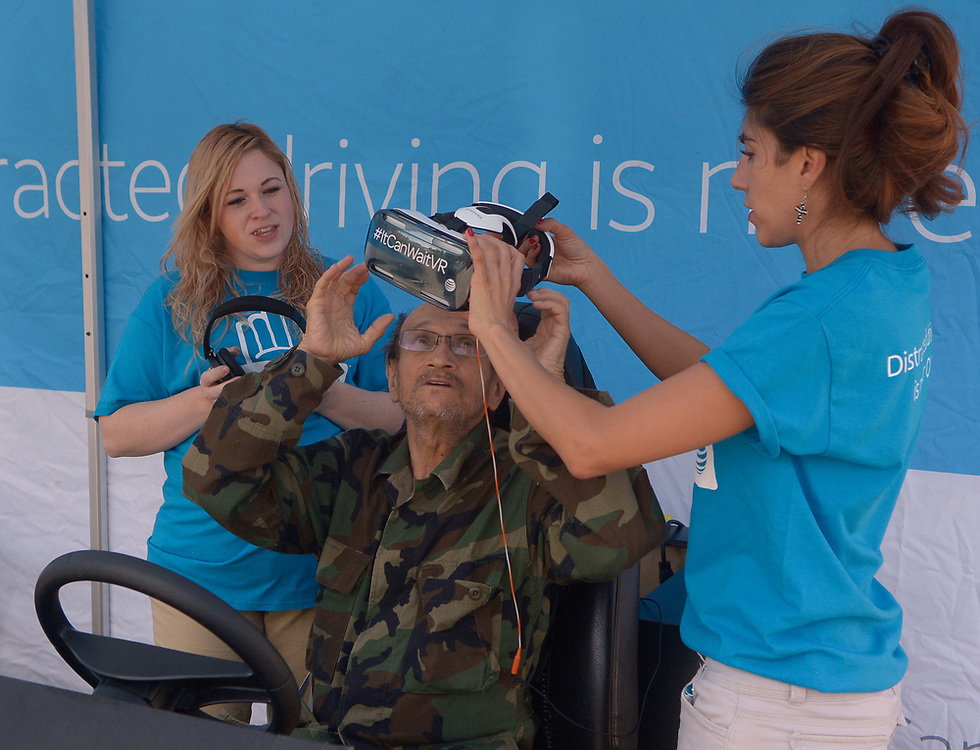 gbs072617h/BUSINESS -- Gregory Bruce Bisulco(cq)of Albuquerque gets a Virtual Reality goggles from Roxanne Martinez, a brand ambassador for AT&T's It Can Wait campaign, right and earphones from ambassador, Leah Juarez, left, during at a safe driving event which shows the dangers of distracted driving, especially with cell phones at the AT&T store at ABQ uptown on Wednesday, July 26, 2017. (Greg Sorber/Albuquerque Journal)