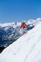 Skier skiing down ski slope side view