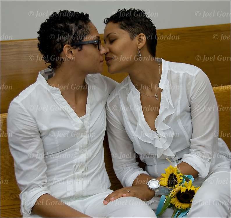 Hispanic American lesbian couple kissing, dressed in white waiting for their marriage certificate to be printed.<br /> <br /> Gay marriage became the law, as 484 couples lined up as early as  7 am, outside the City Clerks's Office in lower Manhattan to take their marriage vows.<br /> <br /> Same-sex marriage in the U.S. state of New York became legal on July 24, 2011 under the Marriage Equality Act, which was passed on June 24, 2011 by the New York State Legislature and signed by Governor Andrew Cuomo on the same day.<br /> <br /> The Marriage Equality Act does not have a residency restriction like some other states and allows religious organizations to decline from officiating same sex wedding ceremonies.
