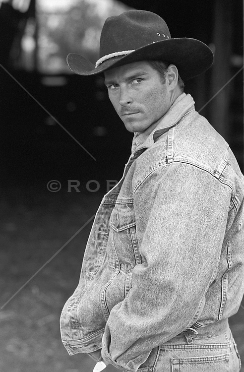 handsome cowboy outdoors near a barn