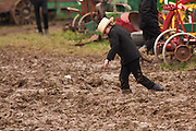 Amish boy walks through thick mud during the Annual Mud Sale to support the Fire Department  in Gordonville, PA.