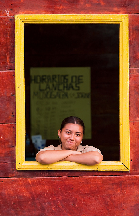 A woman working in a tour agency poses while waiting for tourists to arrive on the next ferry. Tourism has only recently crated jobs on this once isolated island