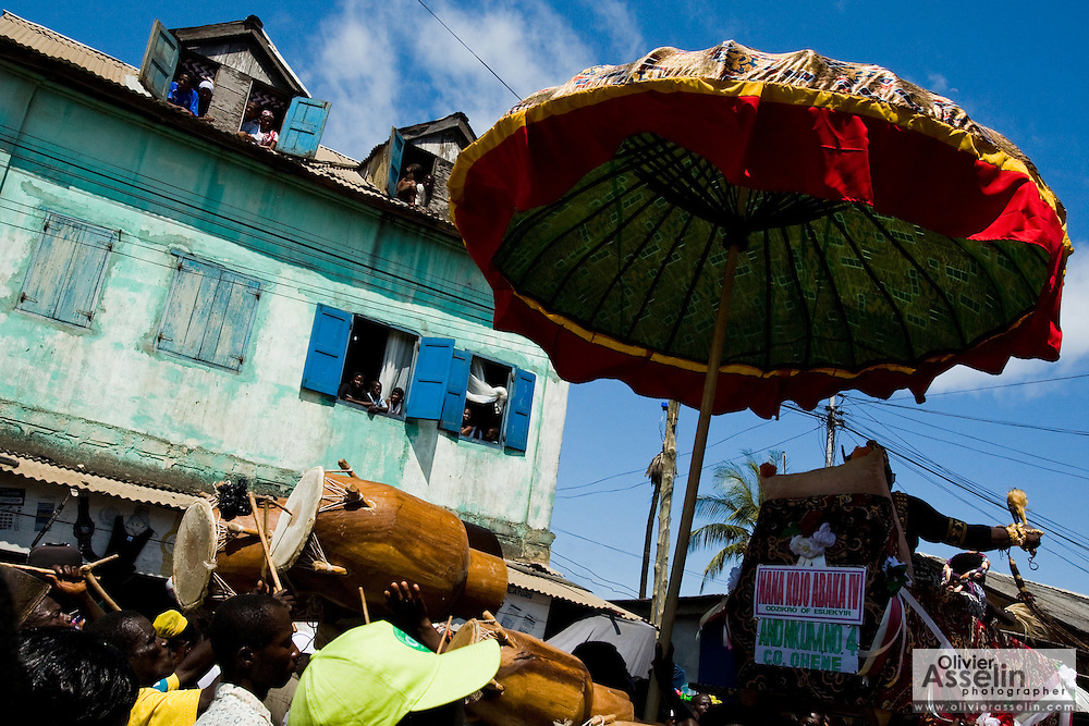 In the shade of a large umbrella, a chief sitting on a palaquin is carried by followers during the parade held on the occasion of the annual Oguaa Fetu Afahye Festival in Cape Coast, Ghana on Saturday September 6, 2008.