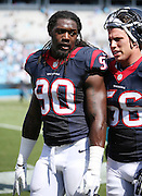 Houston Texans outside linebacker Jadeveon Clowney (90) walks off the field with Houston Texans inside linebacker Brian Cushing (56) after the 2015 NFL week 2 regular season football game against the Carolina Panthers on Sunday, Sept. 20, 2015 in Charlotte, N.C. The Panthers won the game 24-17. (©Paul Anthony Spinelli)