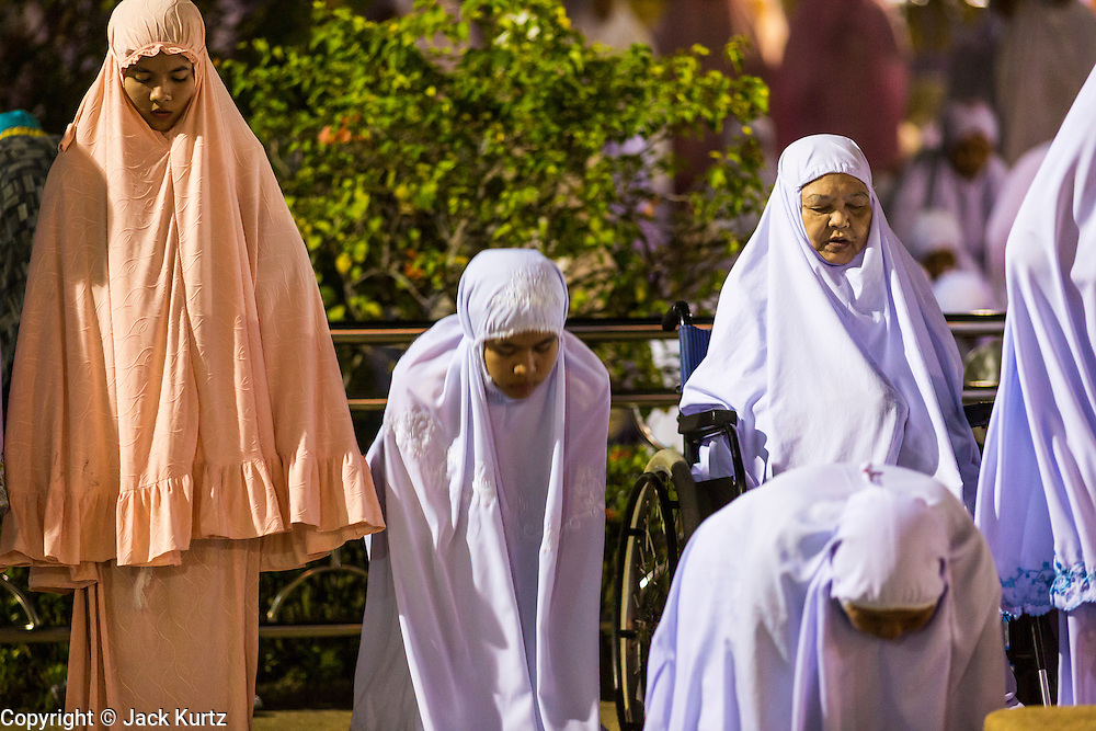 11 JULY 2013 - PATTANI, PATTANI, THAILAND:  Women pray outside of Pattani Central Mosque in Pattani, Thailand, Thursday night for Ramadan services. The mosque is one of the busiest in south Thailand. About 15,000 people attend nightly Ramadan services in the mosque. Ramadan is the ninth month of the Islamic calendar, and the month in which Muslims believe the Quran was revealed. Muslims believe that the Quran was sent down during this month, thus being prepared for gradual revelation by Jibraeel (Gabriel) to the Prophet Muhammad. The month is spent by Muslims fasting during the daylight hours from dawn to sunset. Fasting during the month of Ramadan is one of the Five Pillars of Islam.     PHOTO BY JACK KURTZ