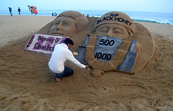 November 13, 2016 - Puri, Bhubaneswar, India - Visitors look near to a sand sculpture to congratulate the new currency note in India, creating by India sand artist Sudarshan Pattnaik at Bay of Bengal Sea's eastern coast beach at Puri, 65 km away from the eastern Indian city Bhubaneswar, India on 13 November 2016. (Credit Image: © Str/NurPhoto via ZUMA Press)