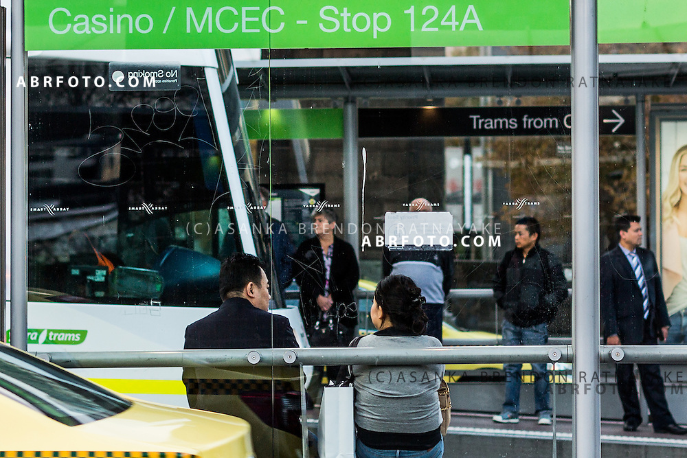 People seated at a tram stop outside crown casino as a yellow taxi drives past Melbourne Victoria Australia