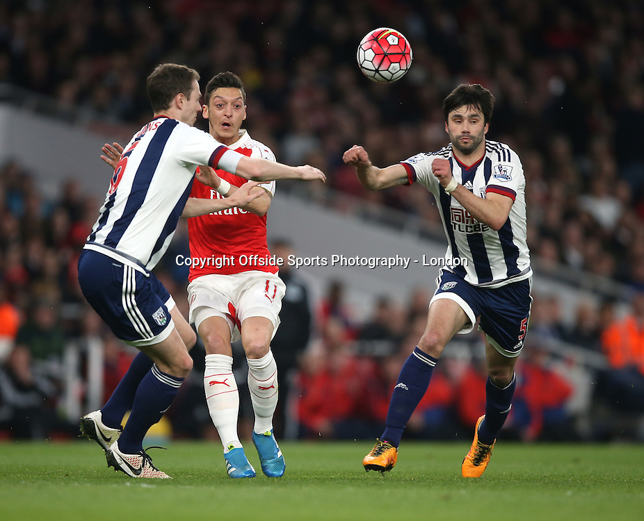21 April 2016  Premier League Football - Arsenal v West Bromwich Albion :<br /> Mesut Ozil makes a pass as Jonny Evans (left) and Claudio Yacob close in.<br /> Photo: Mark Leech