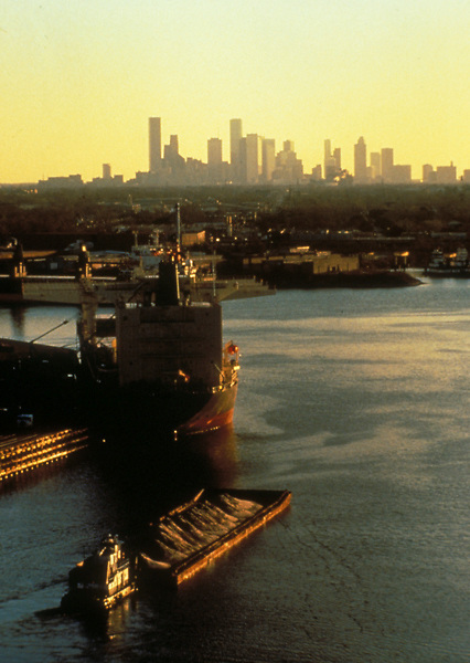 Vessels docked in the Port of Houston in front of the skyline at sunrise.