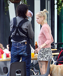 Peaches Geldof, fiancé Thomas Cohen, their baby boy Astala and dog Parpy out in a London park. Peaches wearing a pink cardigan and a short black & white pattern dress took some pictures of the swans before grabing a bite to eat. UK. 13/06/2012<br />