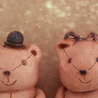 Two small clay model teddy bears standing side by side with one wearing tiny bowler hat and one with hair-ribbon