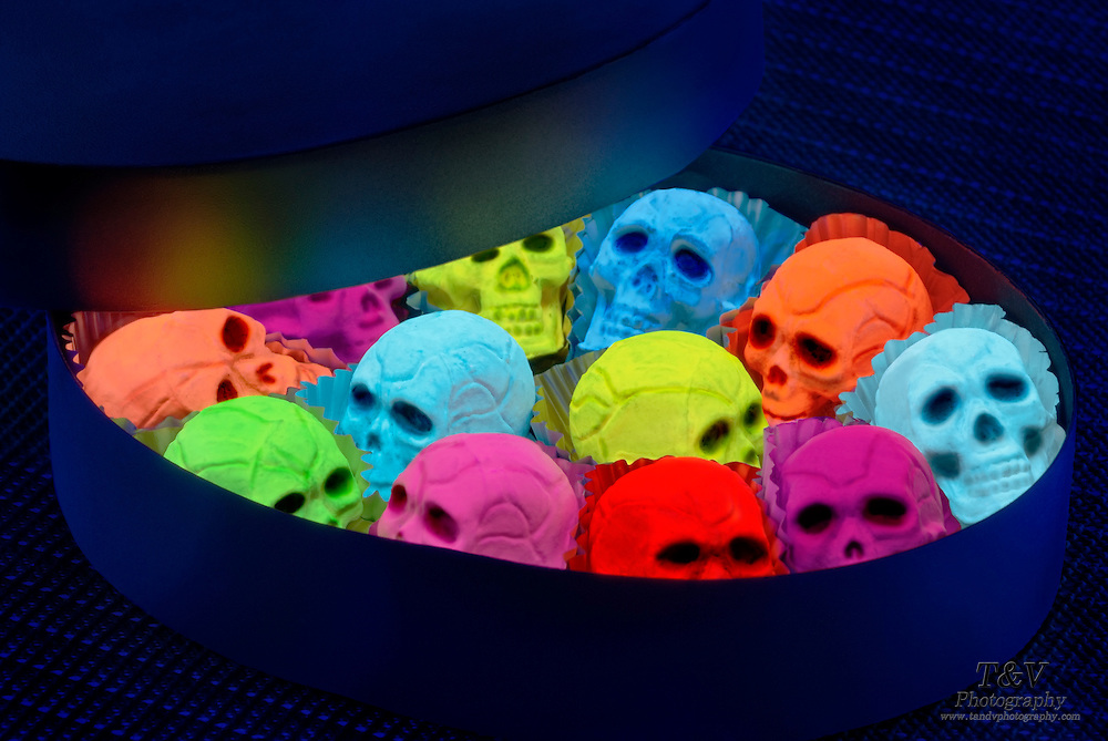 A black gift box filled with minature glowing skulls..Black light