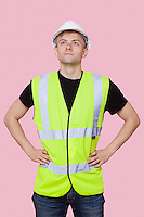 Handsome construction worker with hands on hips over pink background