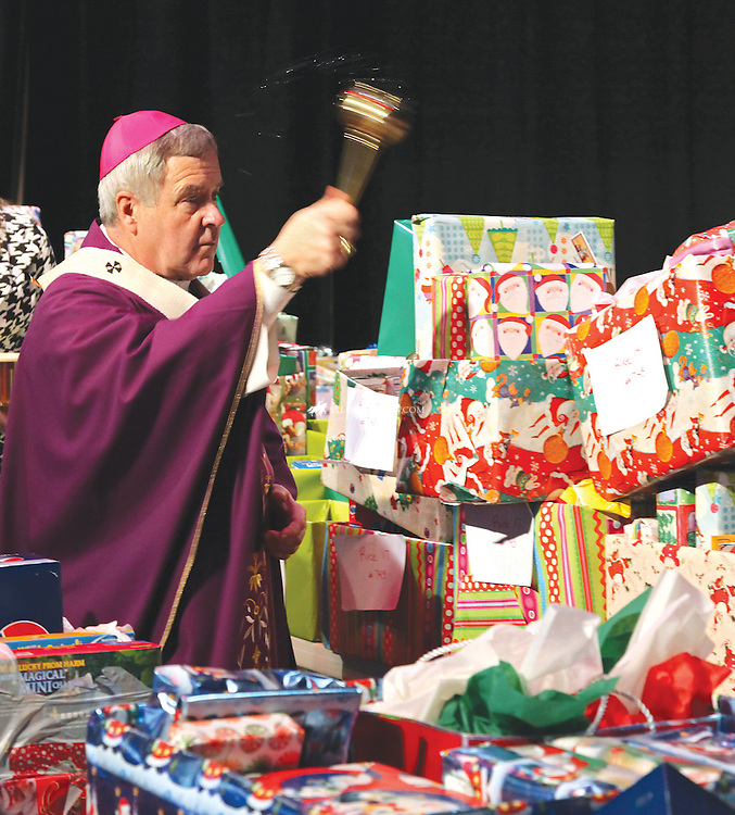 Archbishop Robert J. Carlson blessed the gifts destined for needy families at the 25th annual Adopt-A-Family Mass at Duchesne High School Dec. 17. The stage at the archdiocesan high school in St. Charles was overflowing with Christmas gifts, holiday food items and household necessities, ready for students to deliver them to designated families. Each year Duchesne students have helped 30 or more families, providing a minimum of $10,000 to $12,000 in gifts and food.