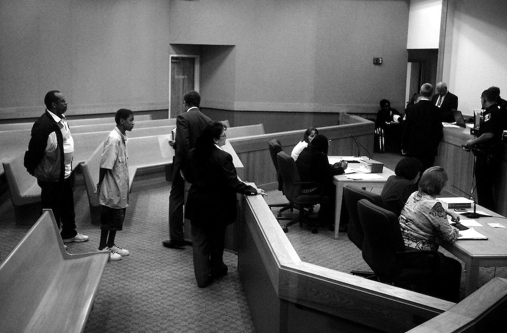Douglas Bolden stands behind his son Marcus, 14, as he appears at the Lee County courthouse on jouvenile charges. Bolden constantly tries to impress upon Marcus that he doesn't want to see him end up in jail like he did. Marcus says he understands, but still finds his way into trouble.  Greg Kahn/Staff