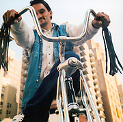 Man sitting on his Schwinn bike with tassels hanging off the handlebars, USA