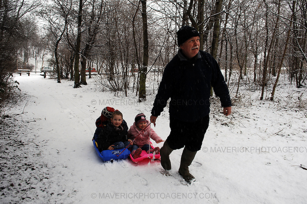 Residents of Edinburgh woke up to the city covered in snow which continued falling into the afternoon...Pic shows Roger Hegarty pulling his grandchildren in sledges behind him in Edinburgh.