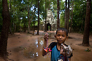 A little boys sells gifts to tourists outside one of the temples.