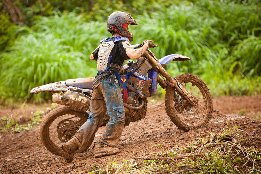 Medium shot shows motocross racer retrieving motorcycle from slope of an extremely muddy outdoor track in Belmopan, Belize.