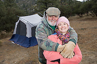 Senior couple embracing in front of tent, portrait