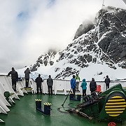 "Passengers on deck admire the dramatic scenery while navigating the Lemaire Channels. The Lemaire Channel is sometimes referred to as ""Kodak Gap"" in a nod to its famously scenic views."