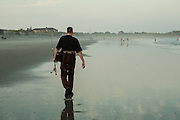 An angler walking on Narragansett Town Beach on a foggy afternoon.